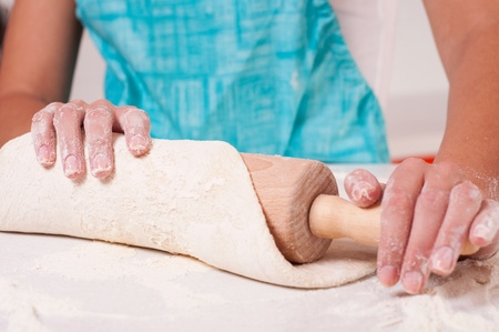Woman hands mixing dough on the table photo