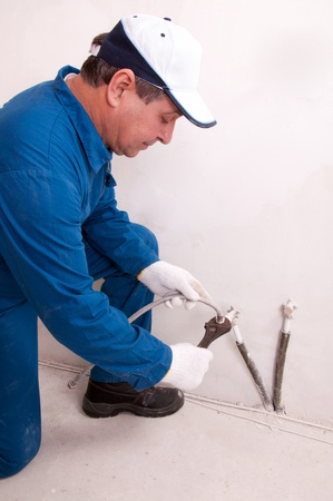 Plumber fixing water pipe photo