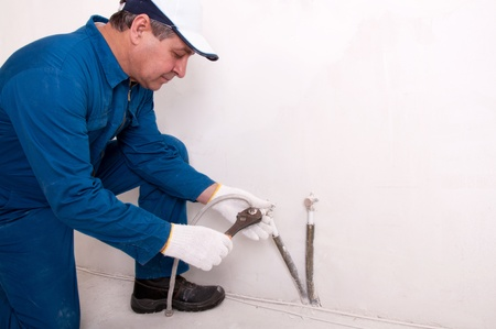 wall of bowel: Plumber fixing water pipe