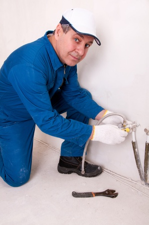 bowel wall: Plumber fixing water pipe