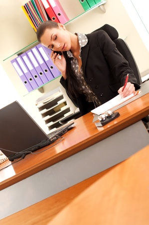 Business woman sitting in the office and making business calls photo