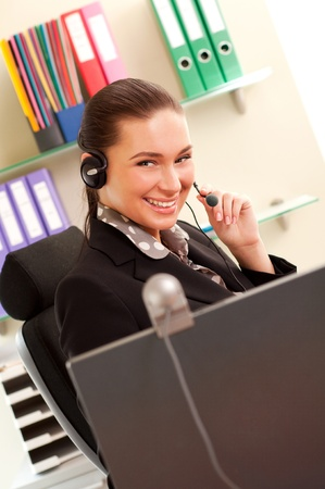 Young business woman working on computer and wearing headphones  photo