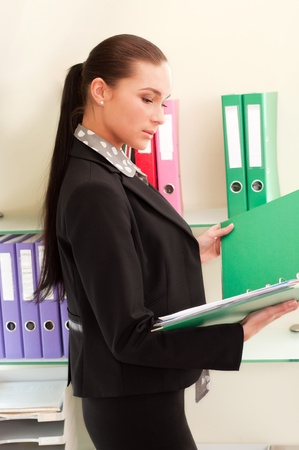 Business woman in front of shelves with folders Stock Photo - 11854306