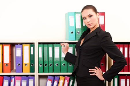 Business woman in front of shelves with folders Stock Photo - 11854036