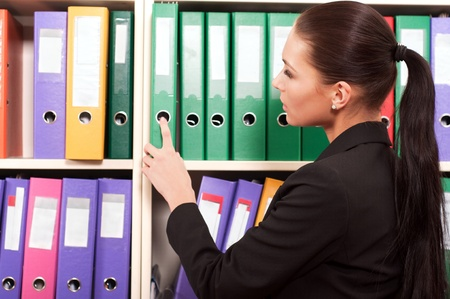 Business woman in front of shelves with folders Stock Photo - 11854374