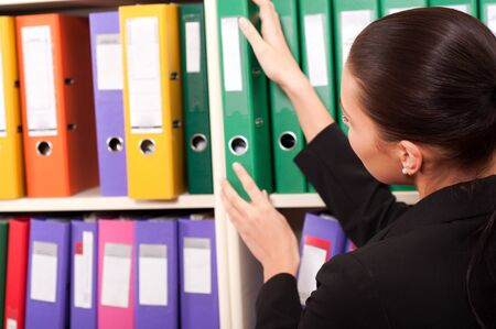 Business woman in front of shelves with folders Stock Photo - 11854357