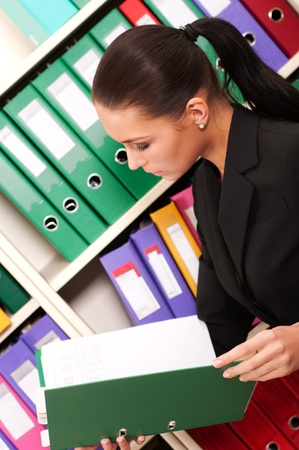 Business woman in front of shelves with folders Stock Photo - 11854336