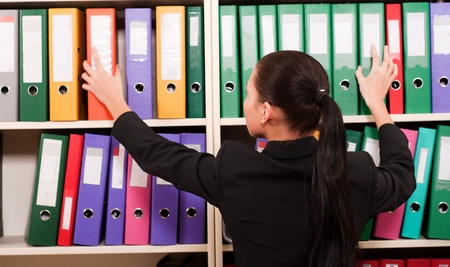 Business woman in front of shelves with folders  Stock Photo - 11854309
