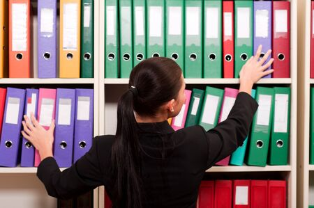 Business woman in front of shelves with folders Stock Photo - 11854348
