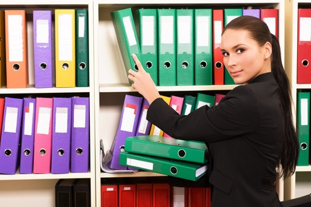 Business woman in front of shelves with folders photo