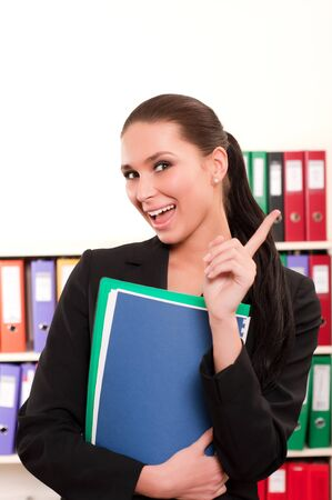 Business woman in front of shelves with folders giving note Stock Photo - 11854139