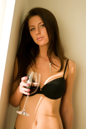 Young woman with perfect body with glass of wine  photo