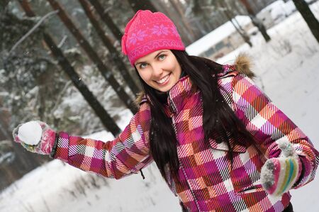 Beautiful young woman outdoor in winter playing snowballs Stock Photo - 12461660