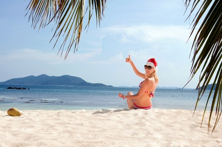Young woman on the beach in santa photo