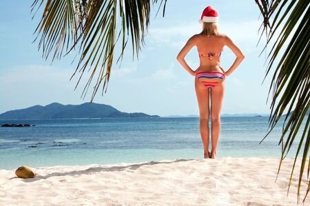 Young woman on the beach in santa's hat  photo