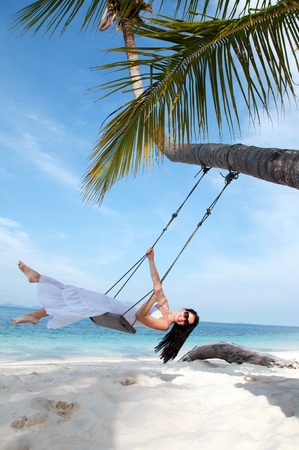 Young woman on the swing on the beach in white dress Stock Photo