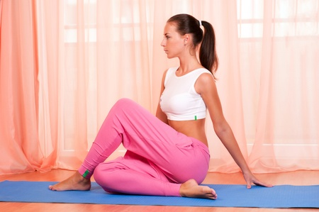 Portrait of pretty young woman doing yoga exercise on mat photo