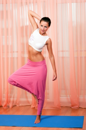 Portrait of pretty young woman doing yoga exercise  photo