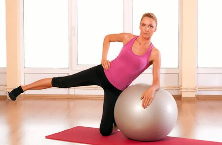 Young woman in sportswear, doing fitness exercise with fit ball. photo