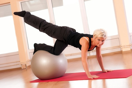 Young woman in sportswear, doing fitness exercise with fit ball. Stock Photo - 12461569