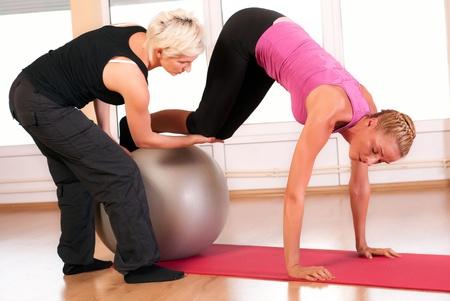 haciendo ejercicio: Entrenador de ayudar a la mujer en hacer ejercicio en la pelota