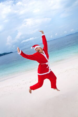 Young woman on the beach in santas costume photo