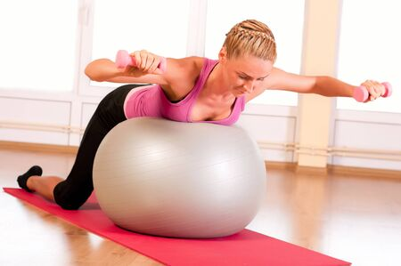 Young woman in sportswear, doing fitness exercise with fit ball and dumbells. photo