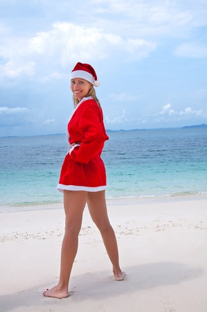 Young woman on the beach in santa's costume photo