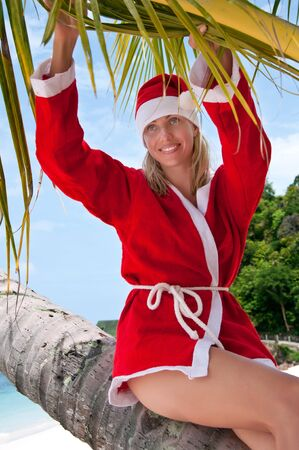 Young woman on the beach in santas costume siting on the palm  photo