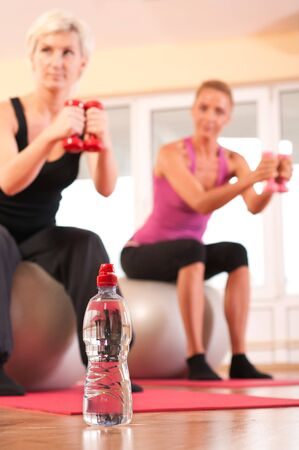 Bottle of water in front of group of people doing fitness exercise photo