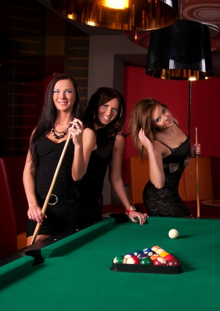 pool tables: Group of happy girls playing in billiard  Stock Photo