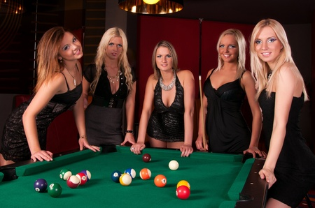 snooker table: Group of happy girls playing in billiard  Stock Photo