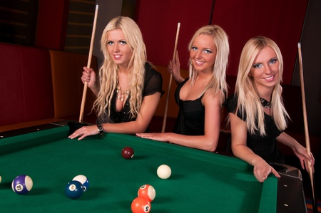billiards tables: Group of happy girls playing in billiard  Stock Photo
