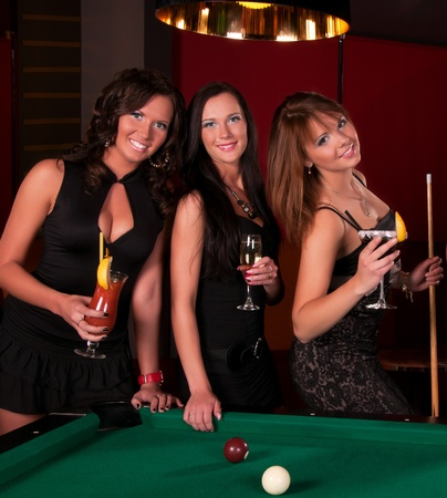 bachelorette party: Group of happy girls playing in billiard  Stock Photo