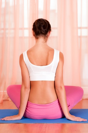 Pretty young woman doing yoga exercise on mat photo