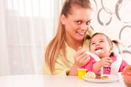 mealtime: Portrait of young woman feeding her baby  Stock Photo