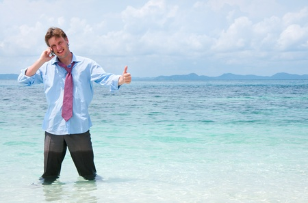 Business man calling by cell phone on the beach  Stock Photo - 12779927