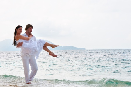 Picture of romantic young couple having a walking on the sea shore  Stock Photo