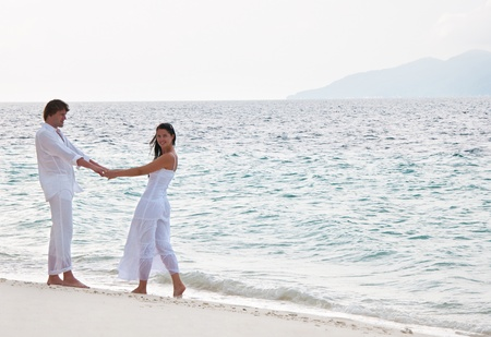 Picture of romantic young couple having a walking on the sea shore  photo