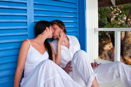 Romantic young couple kissing in tropical beach house photo