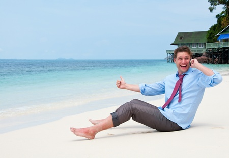 business traveler: Business man calling by cell phone on the beach
