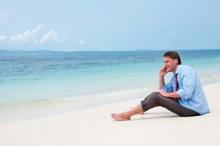 Business man calling by cell phone on the beach photo