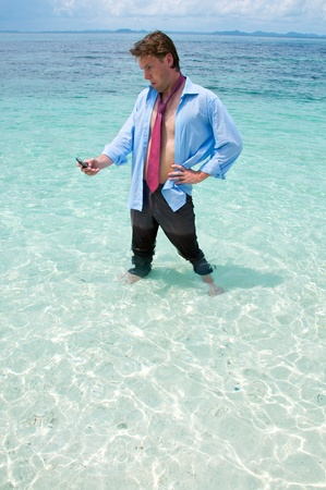 Funny business man calling by cell phone on the beach photo