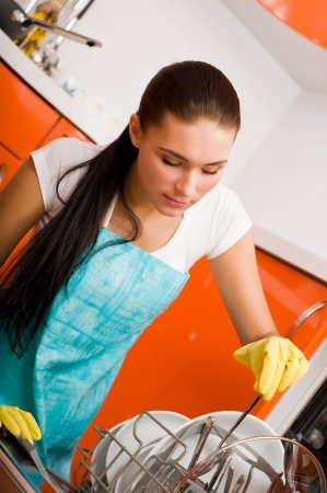 Attractive brunette woman cleaning kitchen using dish washing machine. photo