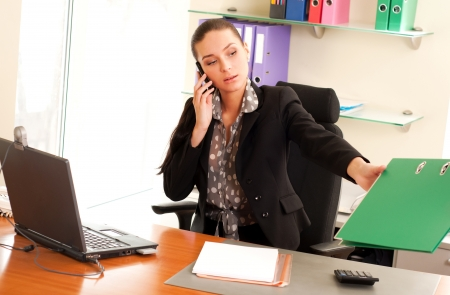 saleswomen: Business woman sitting in the office in front of the laptop and calling by cell phone Stock Photo