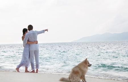 animal lover: Imagen de la joven pareja rom�ntica en la orilla del mar con el perro