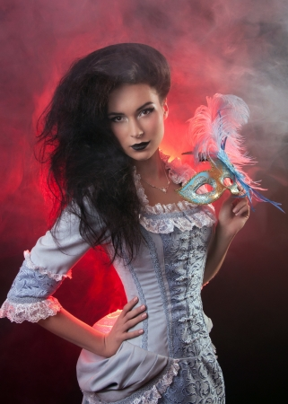 Beautiful Halloween vampire woman aristocrat with venetian mask photo