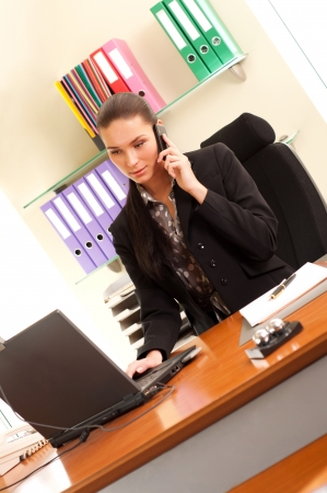 Business woman sitting in the office in front of the laptop and calling by cell phone photo
