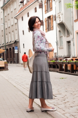 40 45 years: Portrait of smiling brunette woman in town
