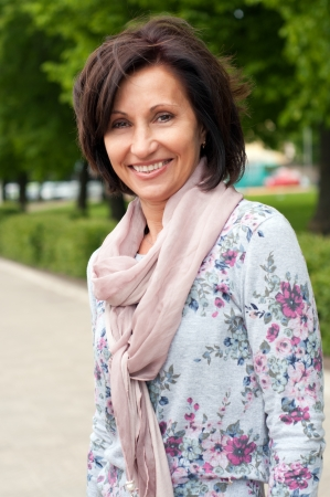 Portrait of smiling brunette woman in park photo